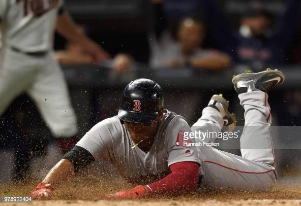 Rafael Devers of the Boston Red Sox slides safely into home plate to score a run against the Minnesota Twins during the eighth inning of the game on...