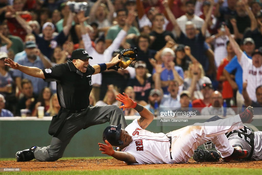 Rafael Devers #11 of the Boston Red Sox slides safely under the tag of Gary Sanchez #24 of the New York Yankees in the fifth inning of a game at Fenway Park on August 19, 2017 in Boston, Massachusetts.