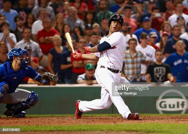 Rafael Devers of the Boston Red Sox strikes out in the bottom of the ninth inning during the game against the Toronto Blue Jays at Fenway Park on...