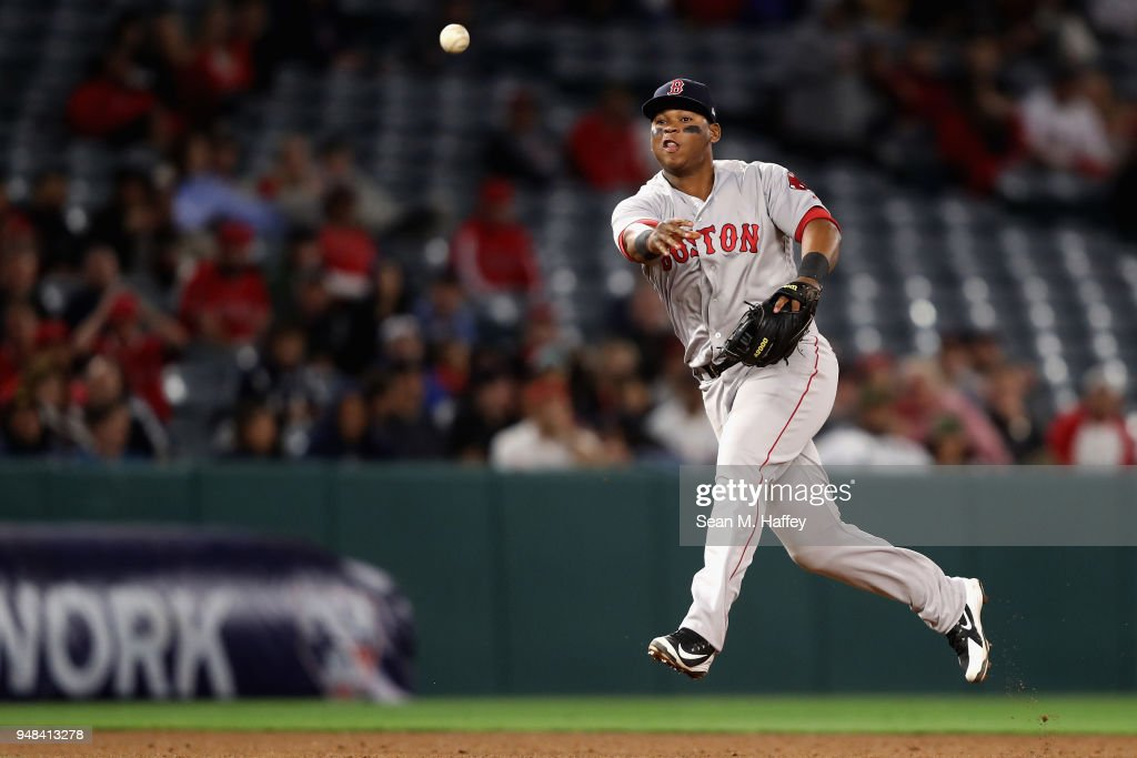 Rafael Devers #11 of the Boston Red Sox throws out Kole Calhoun #56 of the Los Angeles Angels of Anaheim during the eighth inning of a game at Angel Stadium on April 18, 2018 in Anaheim, California.