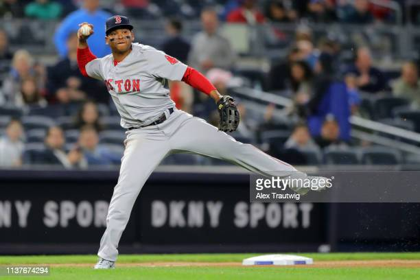 Rafael Devers of the Boston Red Sox throws to first base for the out during the game between the Boston Red Sox and the New York Yankees at Yankee...