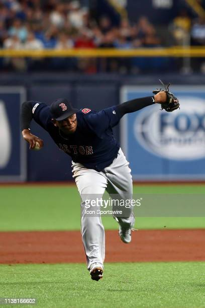 Rafael Devers of the Red Sox hustles in to pick up the ground ball bare handed and then make the throw over to first base during the MLB regular...