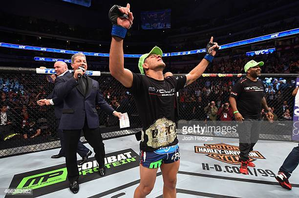 Rafael dos Anjos of Brazil celebrates after being announced the new UFC Lightweight Champion after defeating Anthony Pettis in their UFC lightweight...