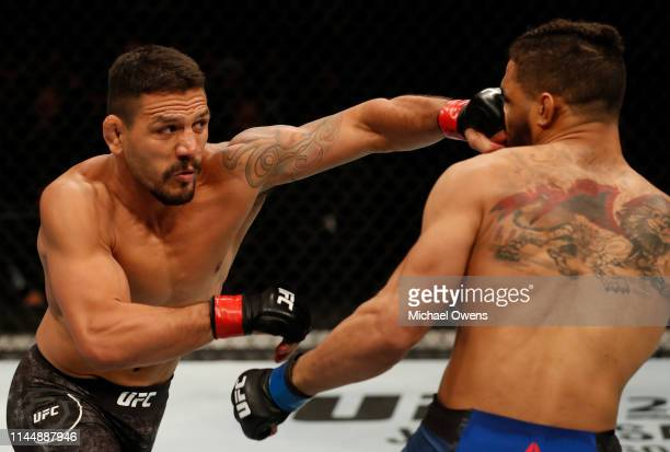 Rafael Dos Anjos of Brazil punches Kevin Lee in their welterweight bout during the UFC Fight Night event at Blue Cross Arena on May 18, 2019 in...