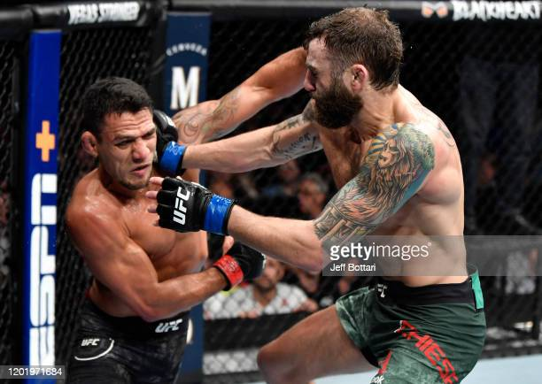 Rafael Dos Anjos of Brazil punches Michael Chiesa in their welterweight fight during the UFC Fight Night event at PNC Arena on January 25 2020 in...