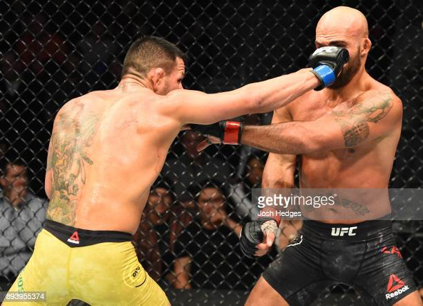 Rafael Dos Anjos of Brazil punches Robbie Lawler in their welterweight bout during the UFC Fight Night event at Bell MTS Place on December 16 2017 in...