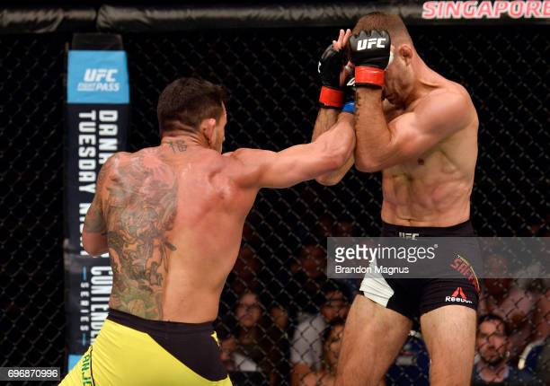Rafael Dos Anjos of Brazil punches Tarec Saffiedine of Belgium in their welterweight bout during the UFC Fight Night event at the Singapore Indoor...