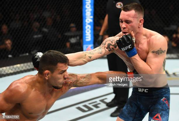 Rafael Dos Anjos of Brazil punches the body of Colby Covington in their interim welterweight title fight during the UFC 225 event at the United...