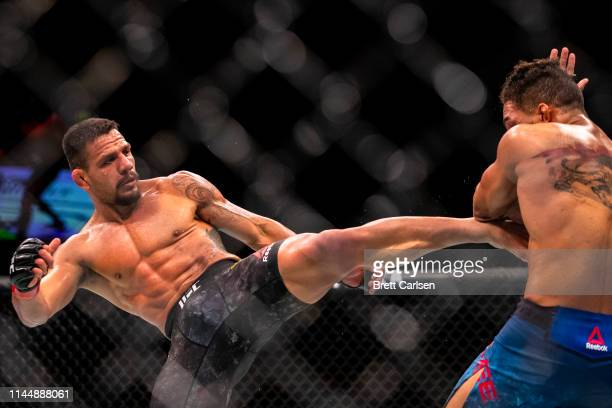 Rafael Dos Anjos throws a kick to the body against Kevin Lee during the third round of a welterweight bout at Blue Cross Arena on May 18, 2019 in...