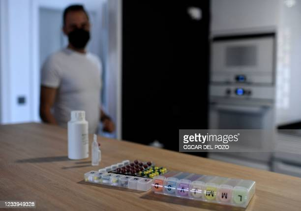 Rafael Garcia looks at his pills in Madrid on July 7 as the roughly 100 pills he must take daily since he received a double lung transplant five...
