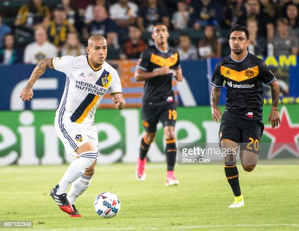 Rafael Garcia of Los Angeles Galaxy is chased by A J DeLaGarza of Houston Dynamo during the Los Angeles Galaxy's MLS match against Houston Dynamo at...
