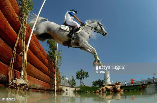 Rafael Gouveia Jr. Of Brazil and horse Mozart clear a jump into water during the team three day eventing cross country competition on August 17, 2004...