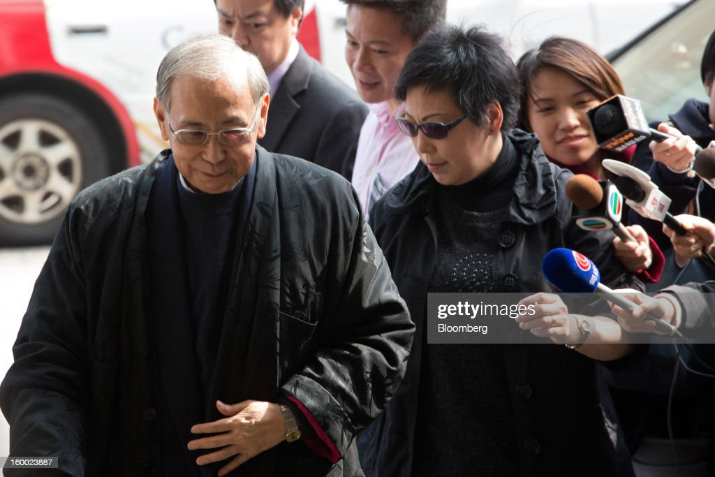 Rafael Hui, Hong Kong's former chief secretary, left, arrives at the Eastern Magistrates' Court in Hong Kong, China, on Friday, Jan. 25, 2013. The prosecution's bribery case against Sun Hung Kai's billionaire co-chairmen Thomas and Raymond Kwok and Hong Kong's former No. 2 official Hui will be ready by March, a court was told. Photographer: Lam Yik Fei/Bloomberg via Getty Images