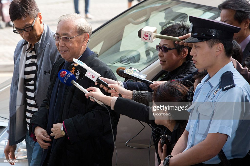 Rafael Hui, Hong Kong's former chief secretary, second left, arrives at the Eastern Magistrates' Court in Hong Kong, China, on Friday, Jan. 25, 2013. The prosecution's bribery case against Sun Hung Kai's billionaire co-chairmen Thomas and Raymond Kwok and Hong Kong's former No. 2 official Hui will be ready by March, a court was told. Photographer: Lam Yik Fei/Bloomberg via Getty Images