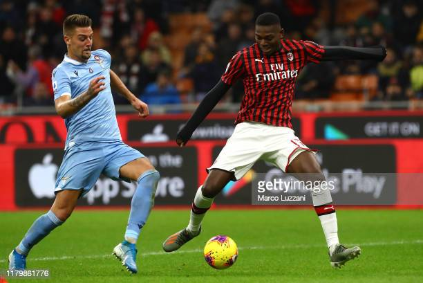 Rafael Leao of AC Milan is challenged by Sergej MilinkovicSavic of SS Lazio during the Serie A match between AC Milan and SS Lazio at Stadio Giuseppe...