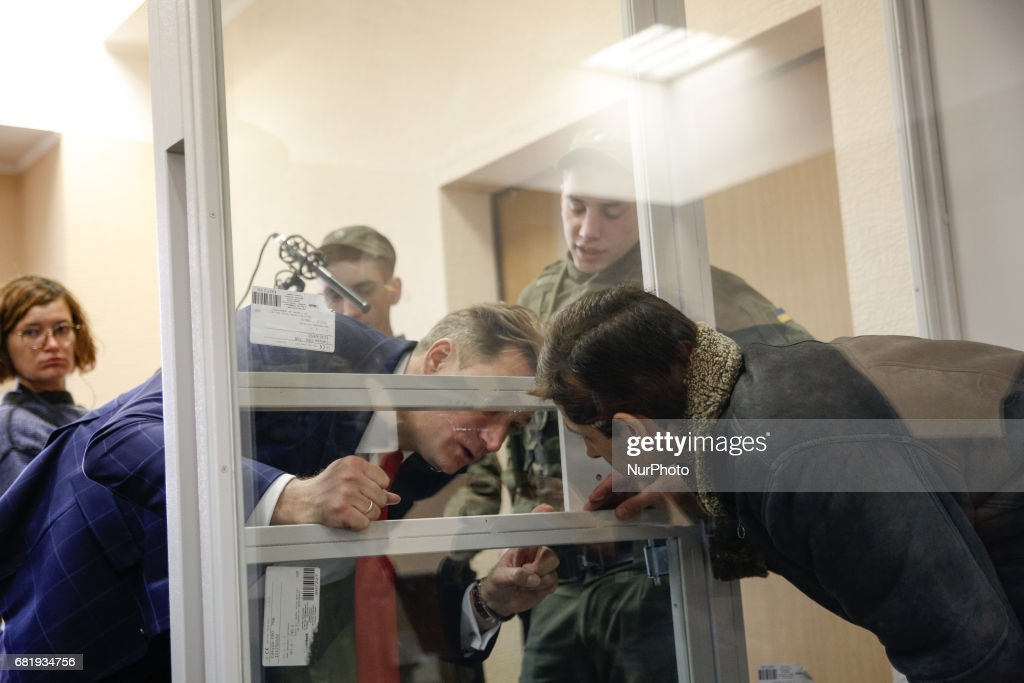 Rafael Lusvarghi is seen talking to his lawyer Valentyn Rybin from the courtroom cage during the trial in Kyiv, Ukraine, May 11, 2017. Appeal court of Kyiv hears the case on Brazilian Rafael Lusvarghi sentenced for 13 years of fighting together with Russia-backed separatists in Ukraine.