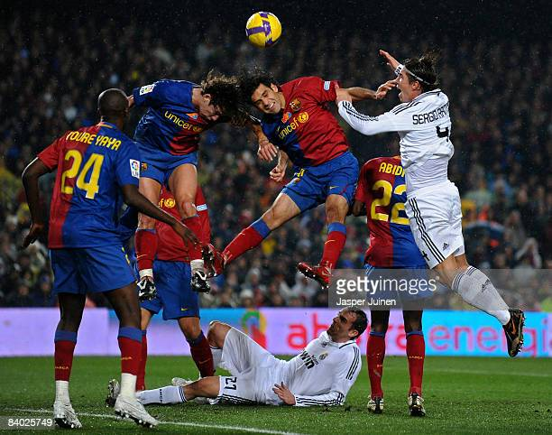 Rafael Marquez and Carles Puyol of Barcelona fight for the ball with Sergio Ramos of Real Madrid as Ramos his teammate Christoph Metzelder lays on...