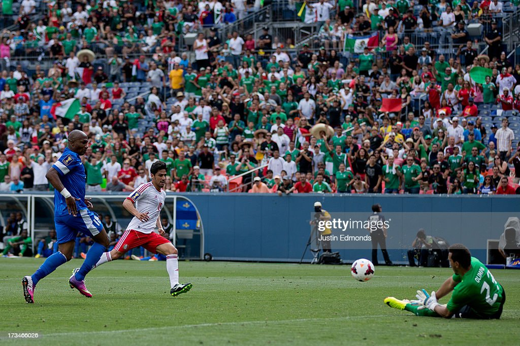 Rafael Marquez Lugo #11 of Mexico has his shot saved by goalkeeper Kevin Olimpa #23 of Martinique as Gregory Arnolin #18 of Martinique trails behind during the first half of a CONCACAF Gold Cup match at Sports Authority Field at Mile High on July 14, 2013 in Denver, Colorado.