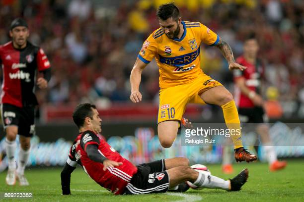Rafael Marquez of Atlas slides for the ball as Andre Gignac of Tigres jumps over during the 8th round match between Atlas and Tigres UANL as part of...