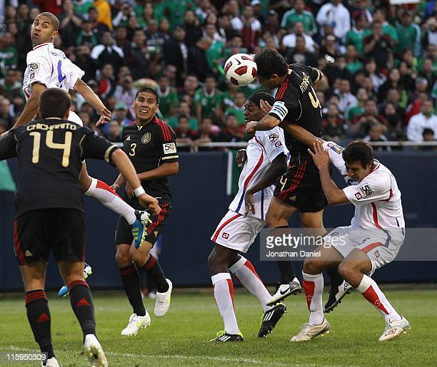 Rafael Marquez of Mexico heads the ball past Alvaro Saborio of Costa Rica for a goal under pressure from Dennis Marshall and Celso Borges during a...