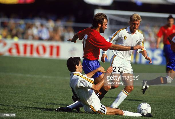Rafael Martin Vazquez of Spain is tackled by Enzo Scifo and Patrick Vervoort of Belgium during the FIFA World Cup Finals 1990 Group E match between...