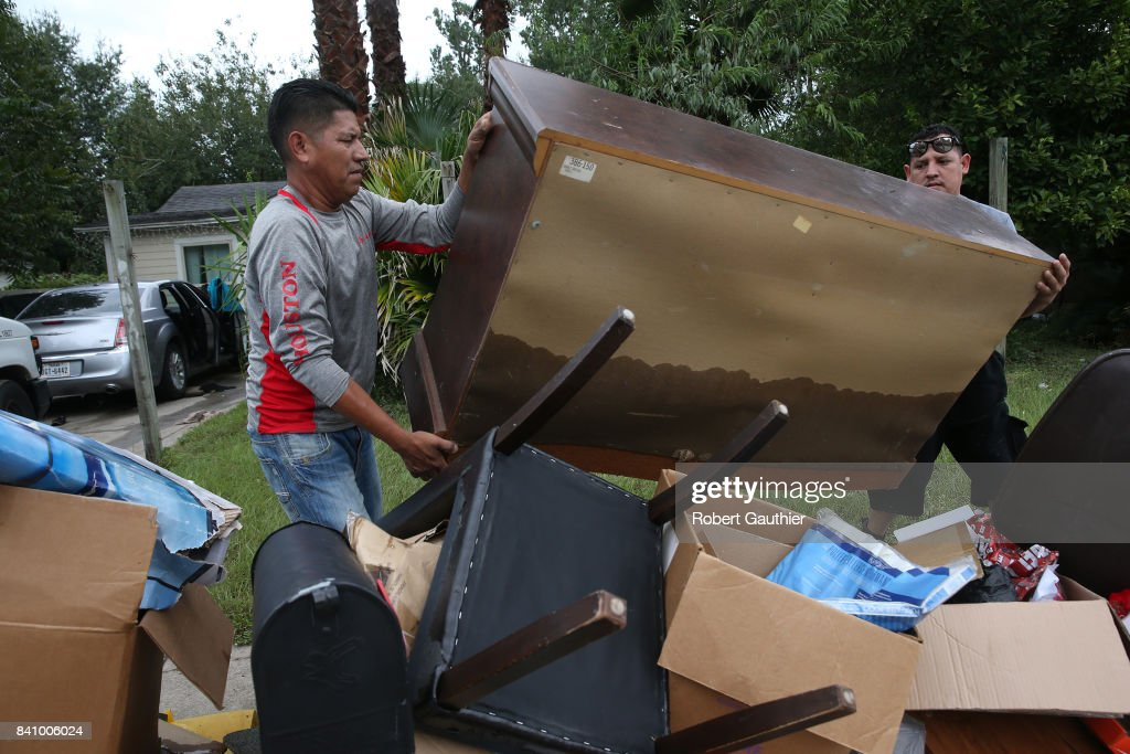 Rafael Minor, left, and Miguel Ramirez remove the contents of Maria Salazar's, 71, Northeast Houston home as residents begin rebuilding from the destruction of Hurricane Harvey on August 30, 2017 in Houston, Texas.