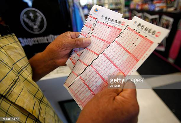 Rafael Moreno picks his lucky numbers as people form a line at Bluebird Liquor located on Hawthorne Blvd at 137th Street in Hawthorne on Monday April...