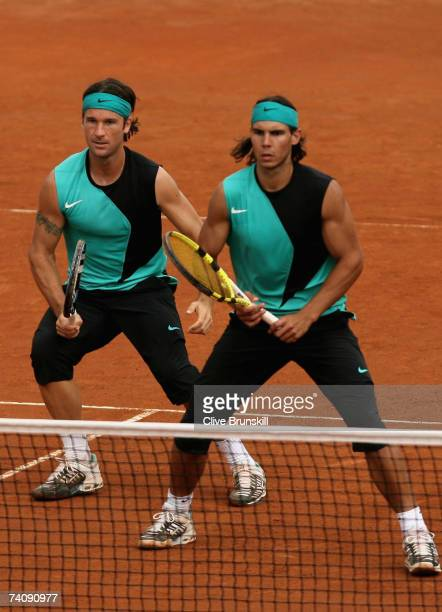 Rafael Nadal and Carlos Moya of Spain in action against Roger Federer and Stanislas Wawrinka of Switzerland in their first round doubles match during...