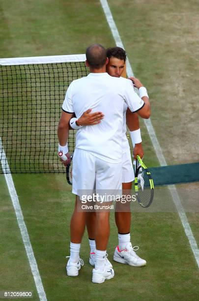 Rafael Nadal of Spain and Gilles Muller of Luxembourg embrace after their Gentlemen's Singles fourth round match on day seven of the Wimbledon Lawn...