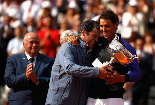 Rafael Nadal of Spain and his coach, Toni Nadal celebrate with the trophy following the mens singles final against Stan Wawrinka of Switzerland on...