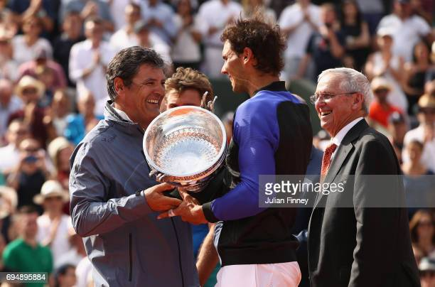 Rafael Nadal of Spain and his coach Toni Nadal pose speak following victory in the mens singles final against Stan Wawrinka of Switzerland on day...
