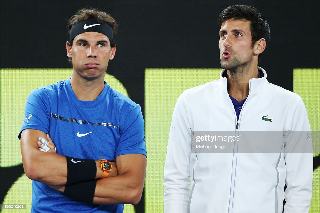 Rafael Nadal of Spain (L) and Novak Djokovic of Serbia hits a forehand react after watching a video replay while on the sidelines during the Tie Break Tens ahead of the 2018 Australian Open at Margaret Court Arena on January 10, 2018 in Melbourne, Australia.
