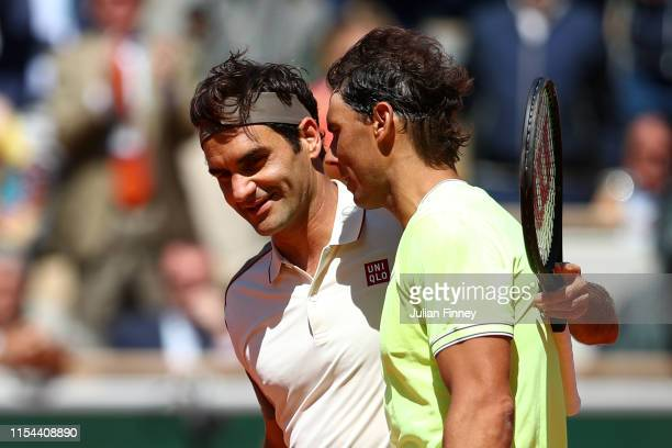 Rafael Nadal of Spain and Roger Federer of Switzerland embrace at the net after their mens singles semifinal match during Day thirteen of the 2019...