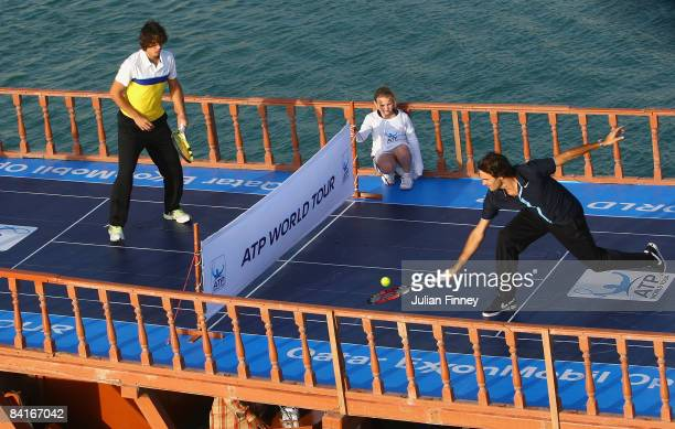 Rafael Nadal of Spain and Roger Federer of Switzerland play tennis on top of a Dhow in Doha Bay to launch the 2009 ATP World Tour during previews for...