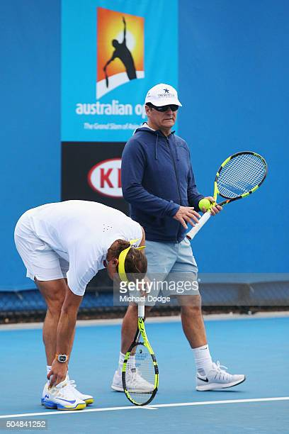 Rafael Nadal of Spain appears to react in pain as he feels his right ankle next to coach Toni Nadal during a practice session ahead of the 2016...