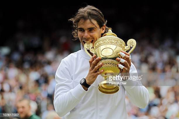 Rafael Nadal of Spain bites the Championship trophy after winning the Men's Singles Final match against Tomas Berdych of Czech Republic on Day...