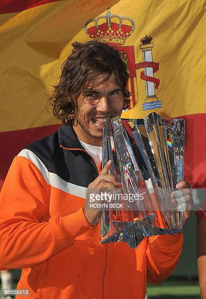 Rafael Nadal of Spain bites the trophy after defeating Andy Murray of Britain in the final of the Indian Wells ATP tennis tournament in Indian Wells...