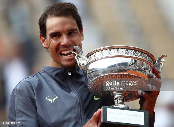 Rafael Nadal of Spain bites the trophy after defeating Dominic Thiem of Austria in the final during Day Fifteen of the 2019 French Open at Roland...
