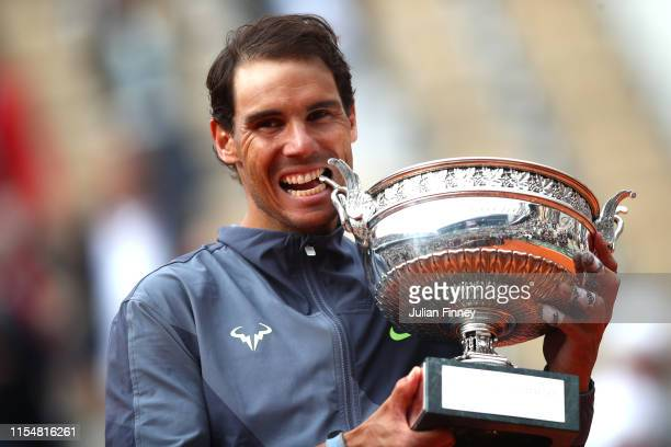 Rafael Nadal of Spain bites the winners trophy after victory following the mens singles final against Dominic Thiem of Austria during Day fifteen of...