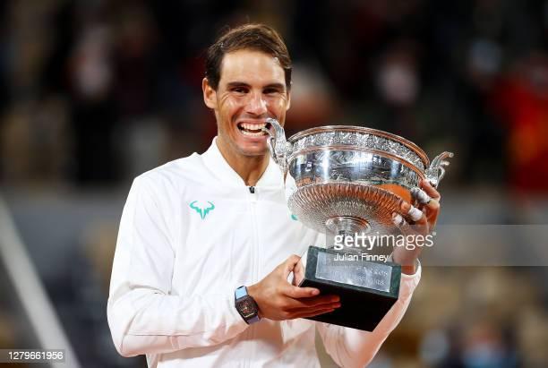 Rafael Nadal of Spain bites the winners trophy following victory in his Men's Singles Final against Novak Djokovic of Serbia on day fifteen of the...
