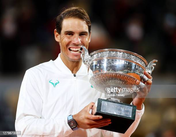 Rafael Nadal of Spain bites the winners trophy following victory in his Men's Singles Final against Novak Djokovic of Serbia on day fifteen of the...