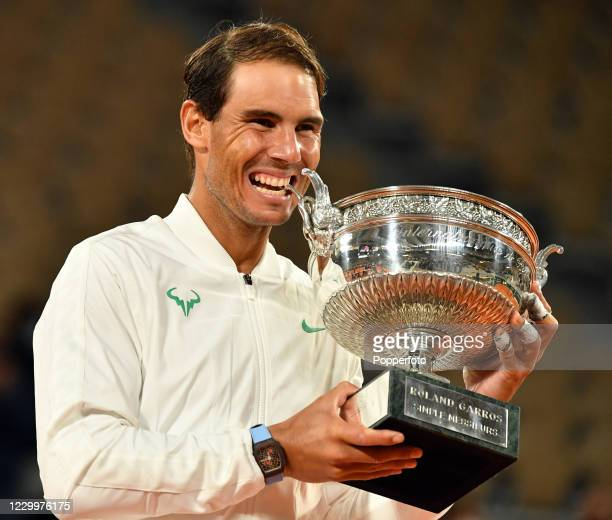Rafael Nadal of Spain celebrates in trademark fashion by biting the La Coupe des Mousquetaires after defeating Novak Djokovic of Serbia in the men's...