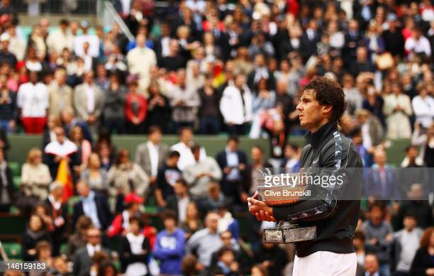 Rafael Nadal of Spain celebrates victory with the Coupe des Mousquetaires trophy in the men's singles final against Novak Djokovic of Serbia during...