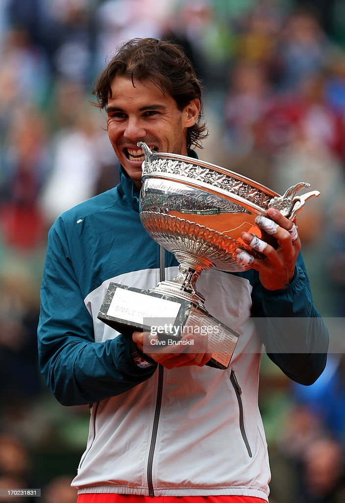 Rafael Nadal of Spain celebrates victory with the Coupe des Mousquetaires trophy in the men's singles final against David Ferrer of Spain during day fifteen of the French Open at Roland Garros on June 9, 2013 in Paris, France.