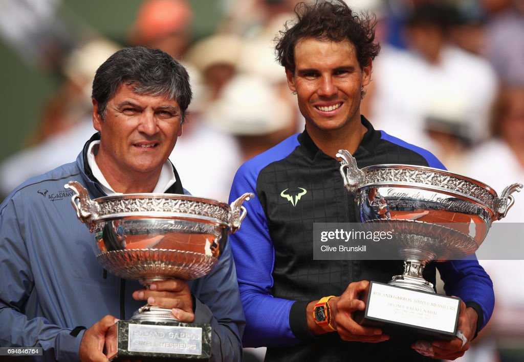 Rafael Nadal of Spain celebrates victory with the trophy alongside coach Toni Nadal after the men's singles final against Stan Wawrinka of Switzerland on day fifteen of the French Open at Roland Garros on June 11, 2017 in Paris, France.