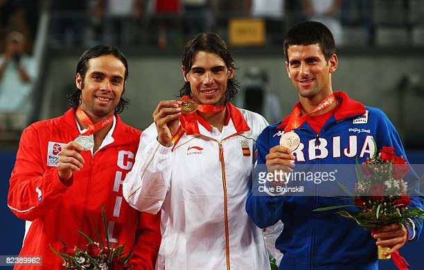 Rafael Nadal of Spain celebrates winning the gold medal with silver medalist Fernando Gonzalez of Chile and bronze medalist Novak Djokovic of Serbia...