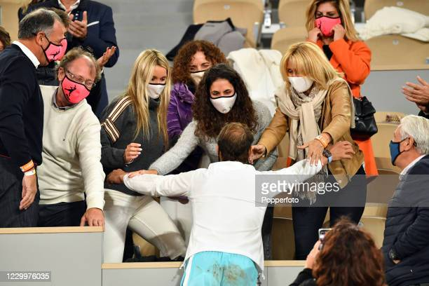 Rafael Nadal of Spain celebrates with his friends and family, all wearing face masks, after defeating Novak Djokovic of Serbia in the men's singles...