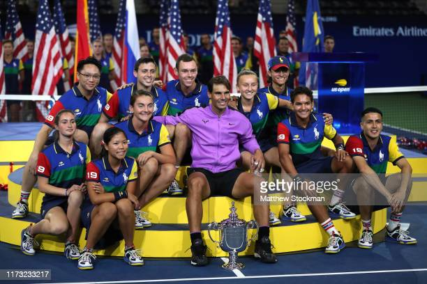 Rafael Nadal of Spain celebrates with the championship trophy alongside the ball people during the trophy presentation ceremony after winning his...