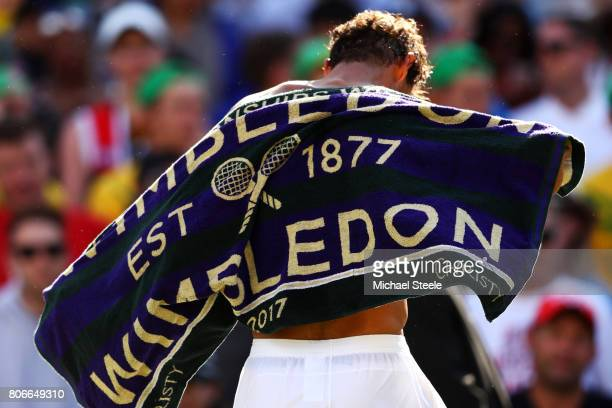 Rafael Nadal of Spain changes his shirt after the Gentlemen's Singles first round match against John Millman of Australia on day one of the Wimbledon...
