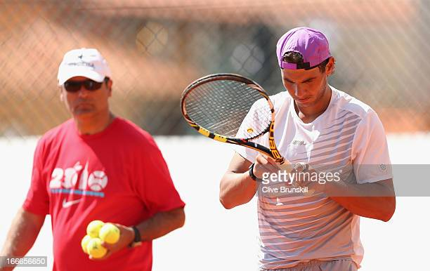 Rafael Nadal of Spain checks his racket grip during a practice session watched by his coach Toni Nadal prior to his second round match during day two...